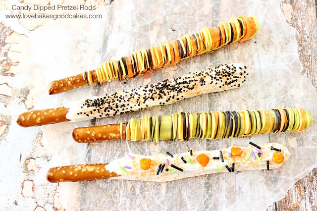 Four candy Dipped Pretzel Rods laying on parchment paper.