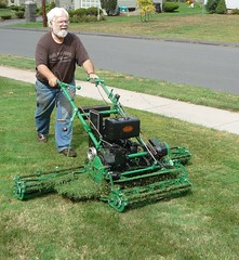 riding mower(0.0), field(0.0), soil(0.0), vehicle(0.0), harvester(0.0), asphalt(1.0), outdoor power equipment(1.0), grass(1.0), tool(1.0), mower(1.0), lawn mower(1.0), lawn(1.0), land vehicle(1.0),
