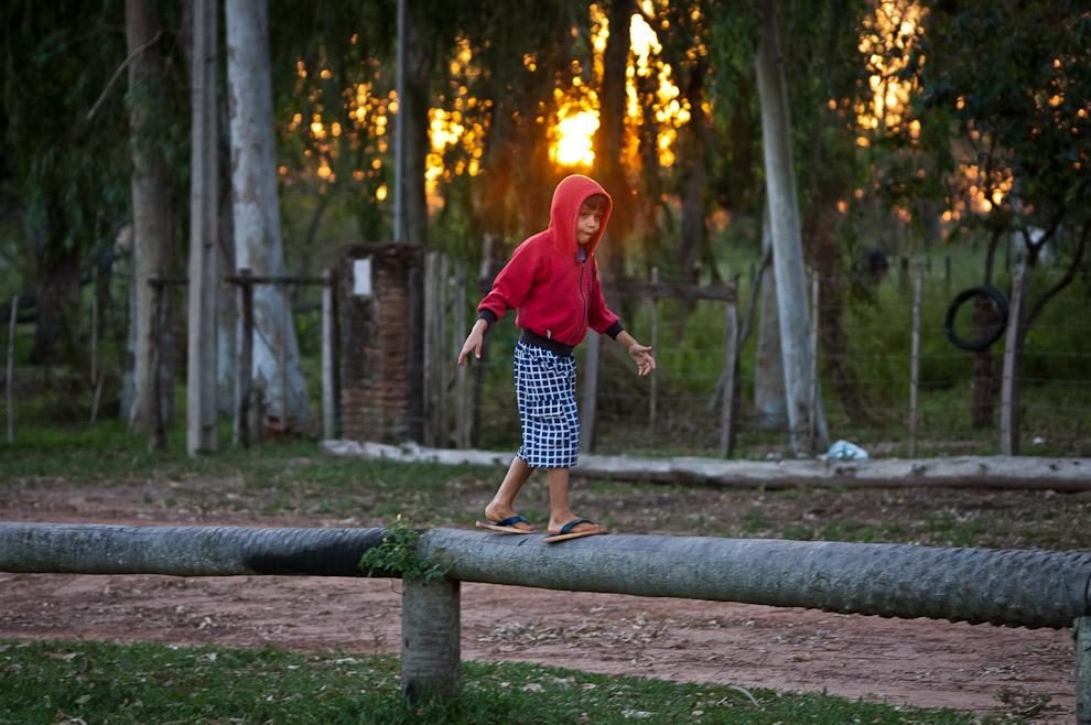Un niño se divierte equilibrandose en los postes de karanda'y en un mirador a orillas del río Jejuí en la ciudad de San Pedro de Ycuamandiyú. (Elton Núñez)