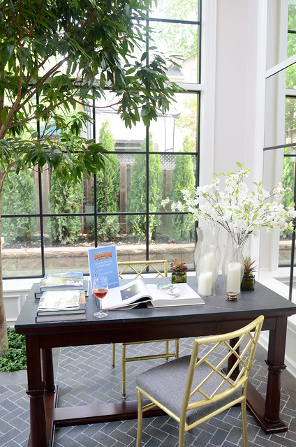 Sun Room office with real tree planted, with dark herringbone flooring: Princess Margaret Showhome in Oakville by Brian Gluckstein