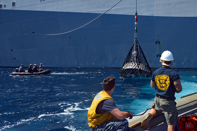 Navy Divers assist Sailors from USS Anchorage in the retrieval of the forward bay cover during the fourth underway recovery test