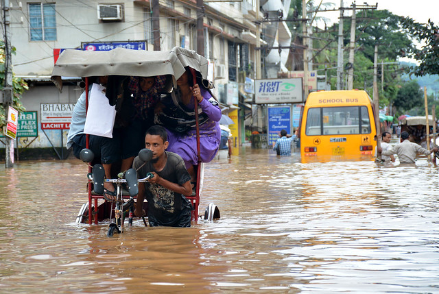 People make their way in flood in Guwahati.