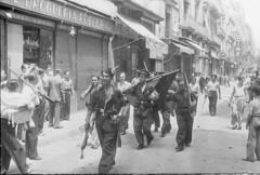 Milicianos en Barcelona. El primero lleva en una mano una lata de sardinas y en la otra una pata de jamón._arxiu Centelles
