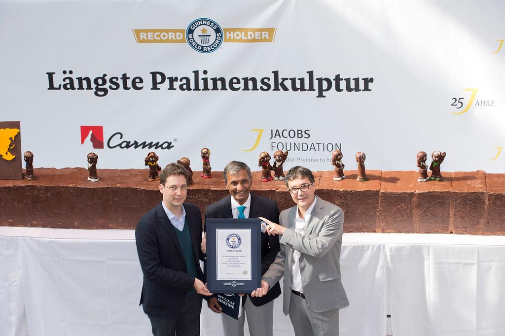 Freuen sich über den Weltrekord: Thomas Hagmann (Geschäftsführer CARMA), Pravin Patel (Guinness World Records Adjudicator), Sandro Giuliani (Geschäftsführer Jacobs Foundation) vor der längsten Pralinenskulptur.