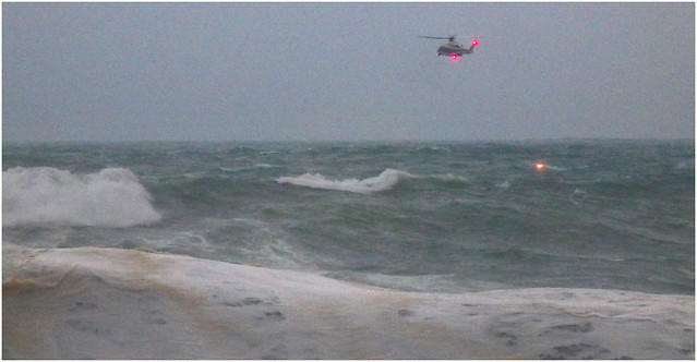 JAPAN COAST GUARD HELICOPTER DROPS A FLARE BESIDE THE LIFELESS BODY OF A U.S. AIRMAN WHO WAS WASHED OUT TO SEA