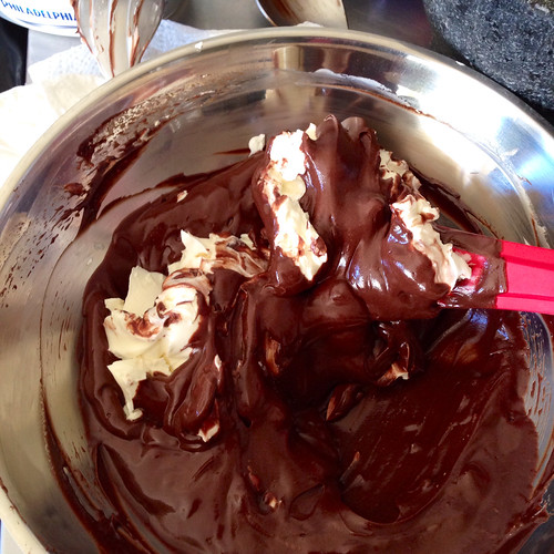 Mixing double cream and chocolate with cream cheese. Food.