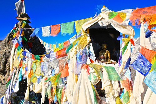 Prayer flags surround a Buddha shrine