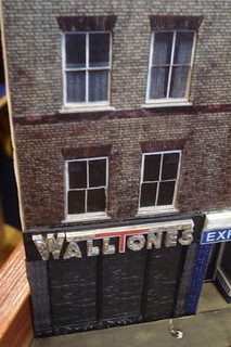 "A model of a three-story terraced building with a ground-floor shopfront reading ""Walltones""."