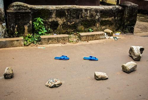 Обувь больного лихорадкой Эбола, отделенная камнями от пешеходной зоны, Фритаун, Сьерра-Леоне. Фото Michael Duff AP