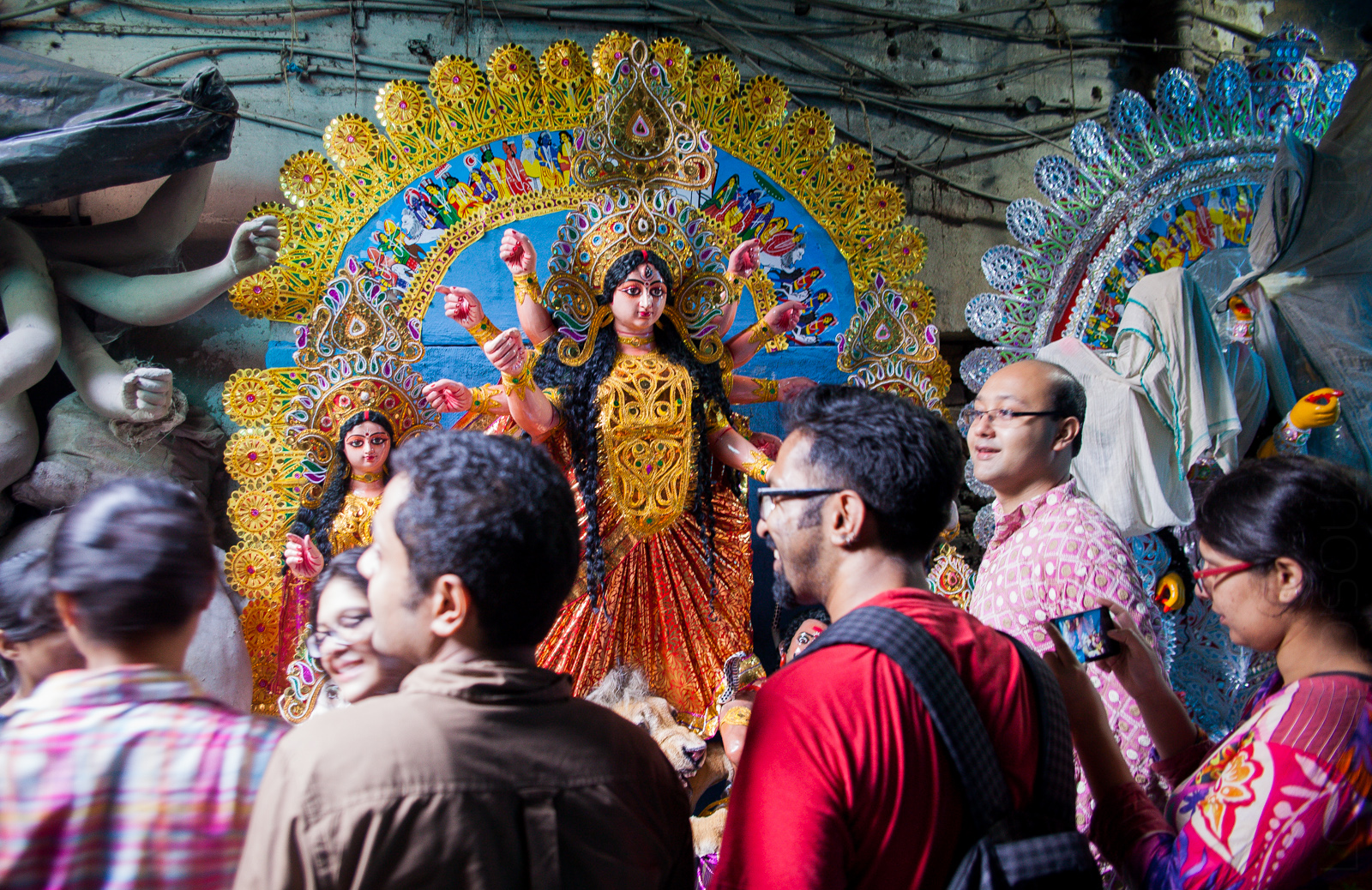 Friends and family share a joke in the presence of Maa Durga