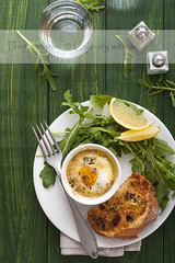 Baked egg with salad and bread on green wood table