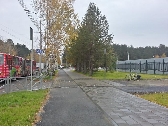 Пересечение тротуара и велодорожки с местным проездом на улице Амундсена