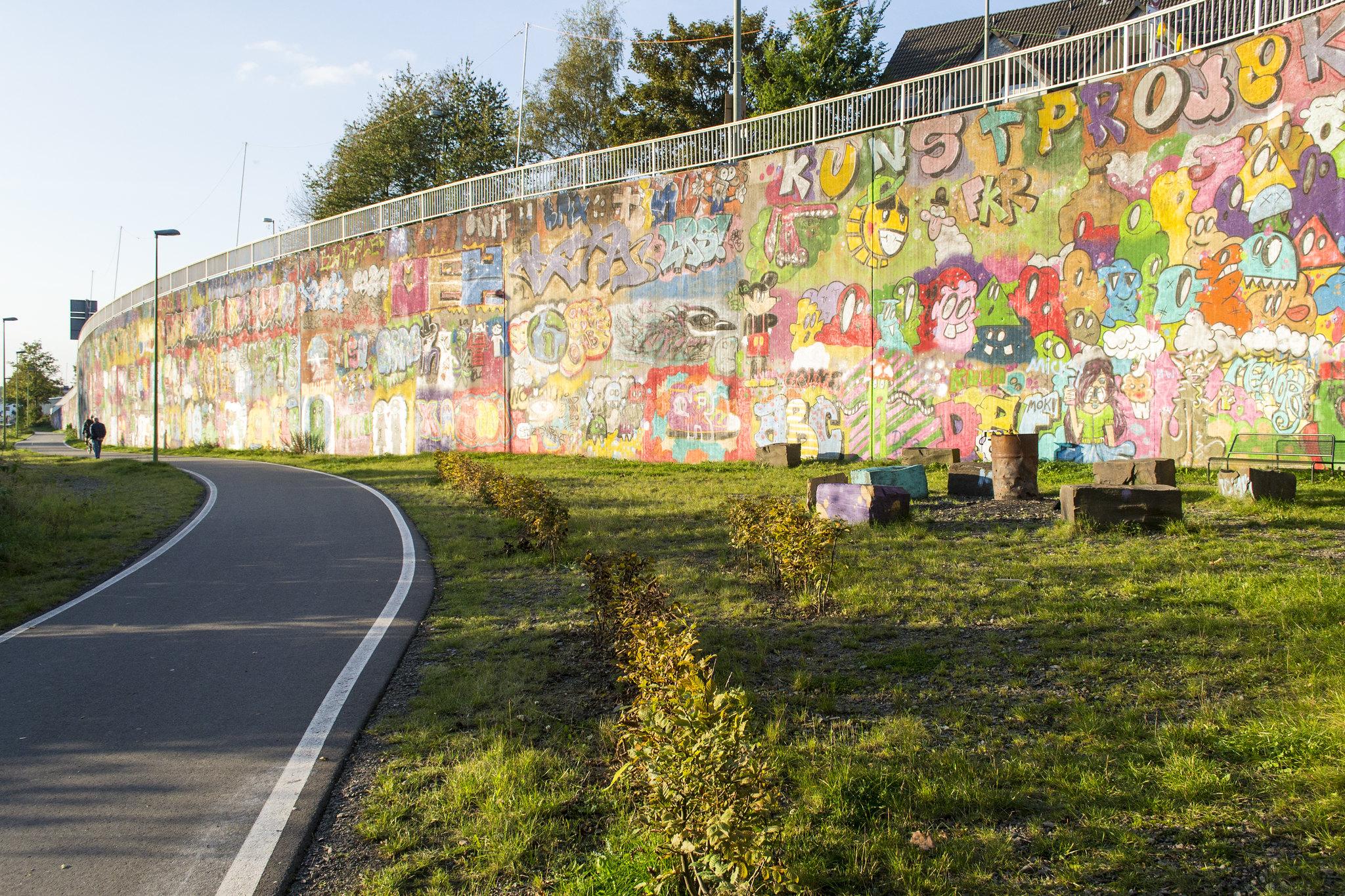 Wall Art/Art Wall: Nichts als Graffiti [Bildbeschreibung: links im Bild verläuft der Radweg, rechts von ihm befindet sich eine Wiese mit einigen einfachen Steinquadern als Sitzmöglichkeiten. Im Hintergrund ragt eine geschwungene Betonwand mit Geländer auf, die dem Straßenverlauf der höher gelegenen Straße folgt. Diese Wand ist voller Graffiti, vorwiegend Gesichtern.]