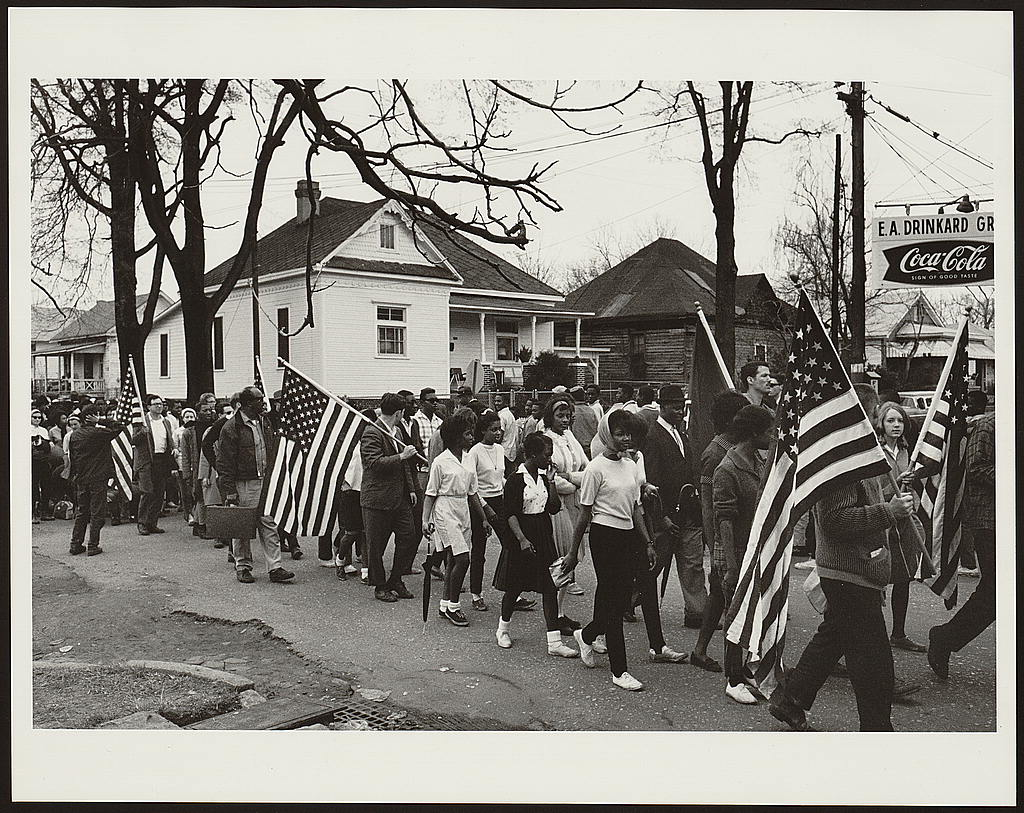 [Participants, some carrying American flags, marching in the civil rights march from Selma to Montgomery, Alabama in 1965] (LOC)