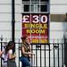 Tourists passing London UK hotel window billboard advertising cheap rooms at £30 per night