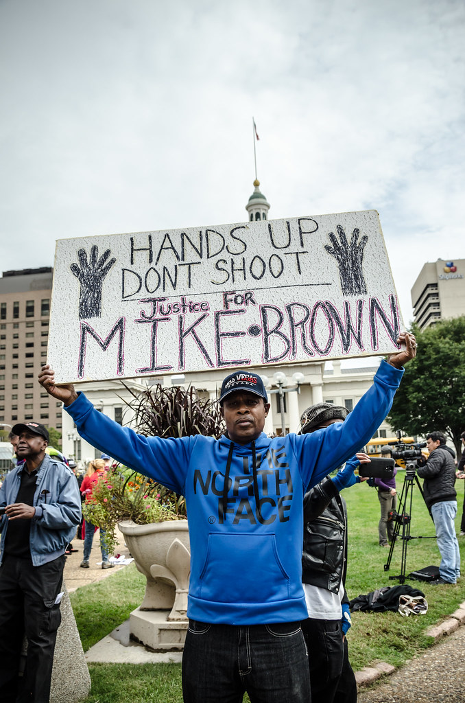 "a photo shows a man holding a sign that says ""hands up don't shoot"""