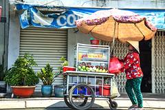 Woman pushing fruit cart on An Duong Vuong--Saigon
